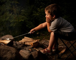 A boy sitting next to a campfire